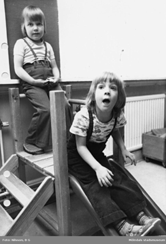 Två barn i en liten rutschbana inomhus. Holtermanska daghemmet maj 1975.