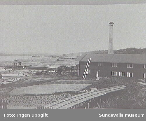 Johannesnäs såghus med timmerkiratt och kajanläggning. Stugan på kajen disponerades av timmermottagaren som övernattningsstuga. Johannesnäs sågverk hette före 1906 Johannesvik. I bakgrunden Hovids sågverk.