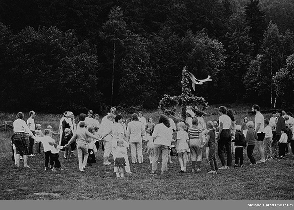 Bilden är från ängen vid daghemmet. Varje år samlades barn, föräldrar och personal för att fira midsommar. Blommor plockades dagen före och kl 9 på midsommaraftonen samlades man och klädde stången samt gjorde kransar. Kl 11 restes stången, sedan började dansen med spelemän ur personalen. Dansen avslutades med godiskastning. Sedan åt man köttbullar eller sill, glass till efterrätt, vid långbord utomhus. Vid regn åt man i daghemmets/förskolans lekhallar.