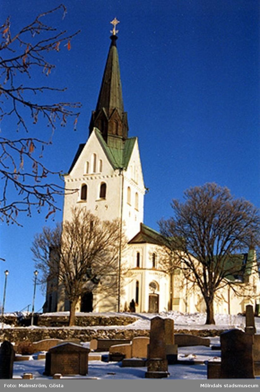 Vy från vänster med tornet i förgrunden. Framför kyrkan ligger kyrkogården.