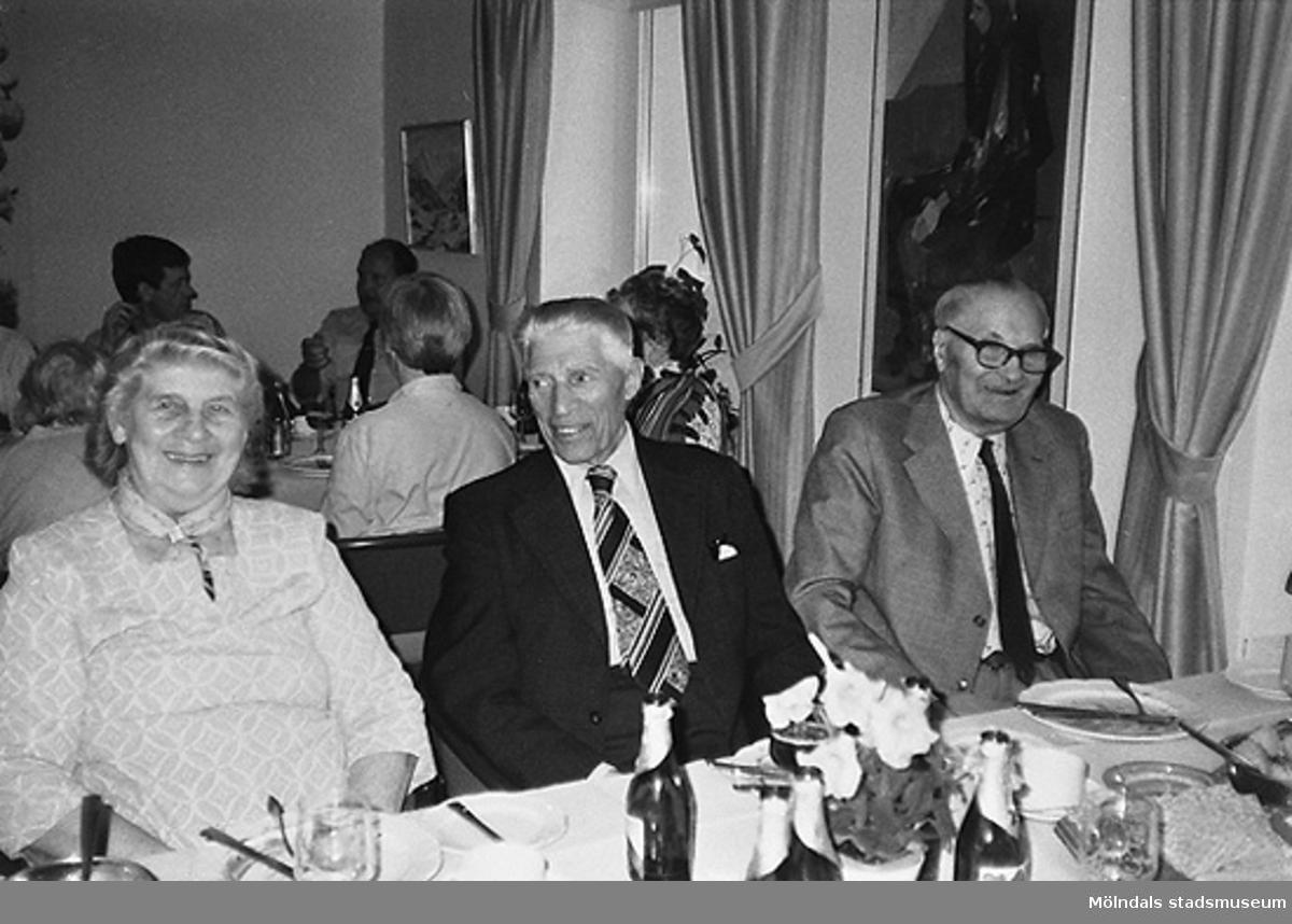 I förgrunden sitter tre välklädda och leende personer vid ett bord. De har nyss ätit en måltid. I bakgrunden sitter fler personer vid andra bord. Okänt årtal.