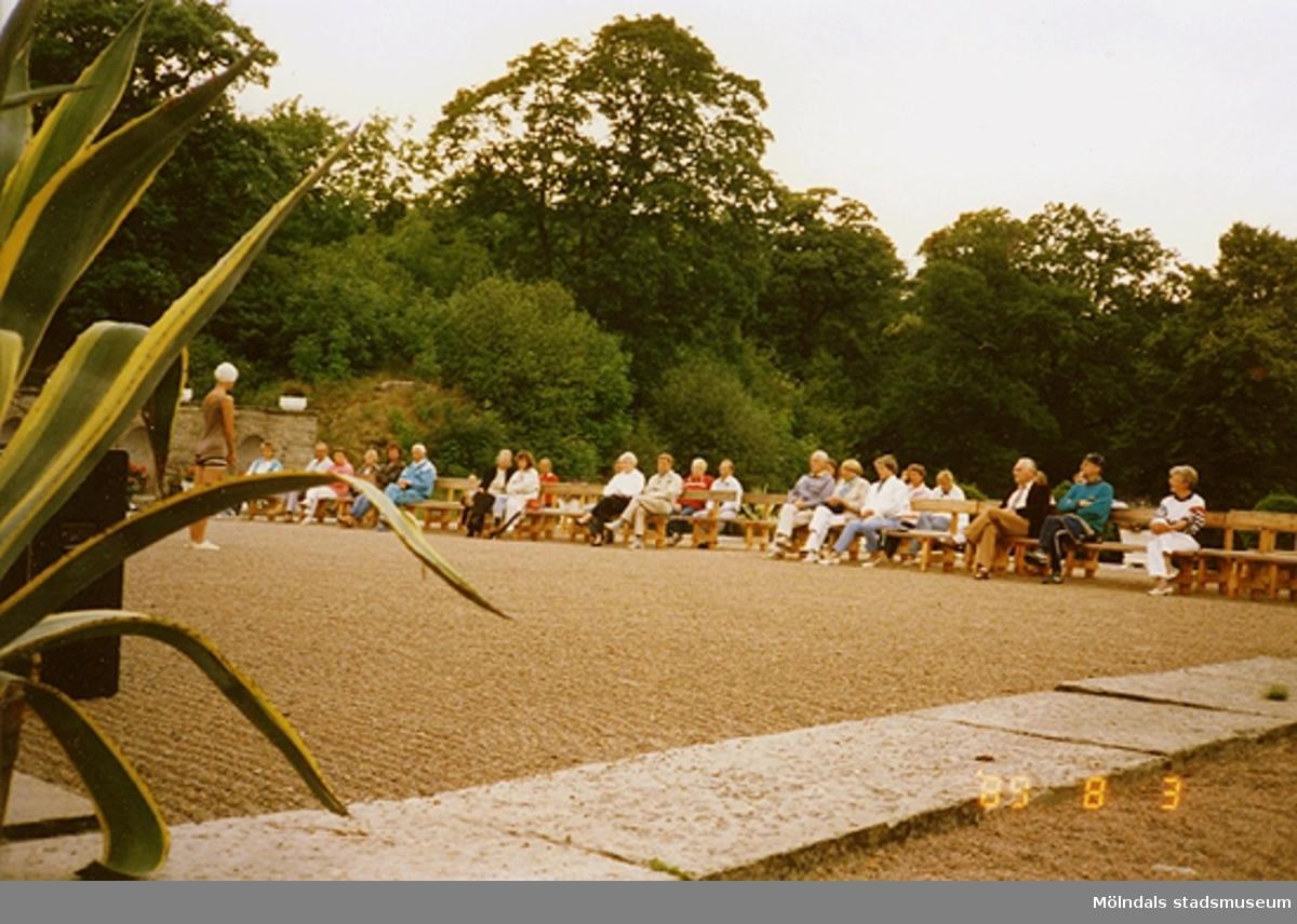 Publik sitter på bänkar och tittar på en dansuppvisning.