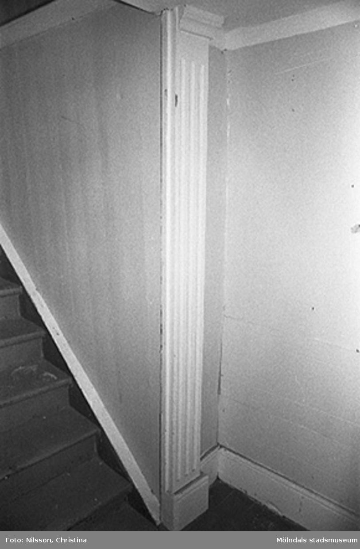 Interiör från Röda husets undervåning. Bilden visar del av förstugan och trappan till övervåningen. Ornerade pilastrar var vanligt förekommande inom den s.k schweizerstilen som i Sverige uppfattades som urnordisk och därför gärna efterliknades i arkitekturen. Man trodde att stilens former uttalade ett nordiskt arv vilket eftersöktes under 1800-talet. En dörr har tidigare funnits för trappuppgången.