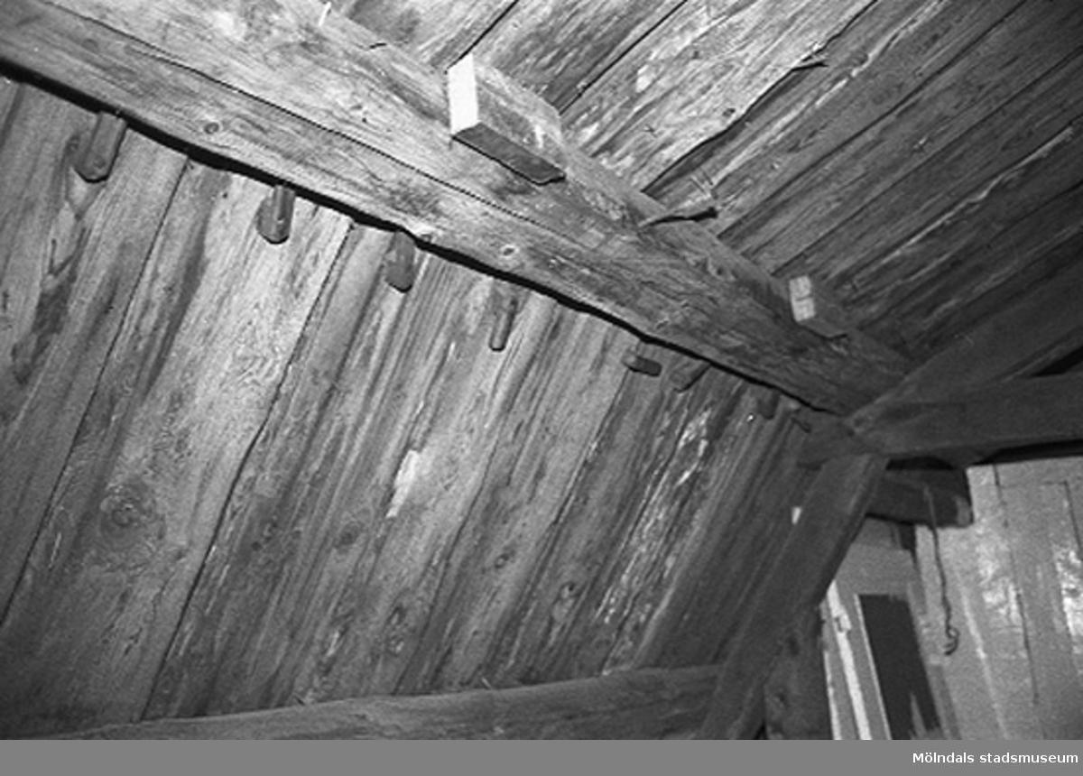 Röda huset, G-3. Interiör från den oinredda delen av vinden. Bilden visar del av det brutna sadeltaket som bärs upp av åsar. Vad träkrokarna vid åsen använts till är oklart.