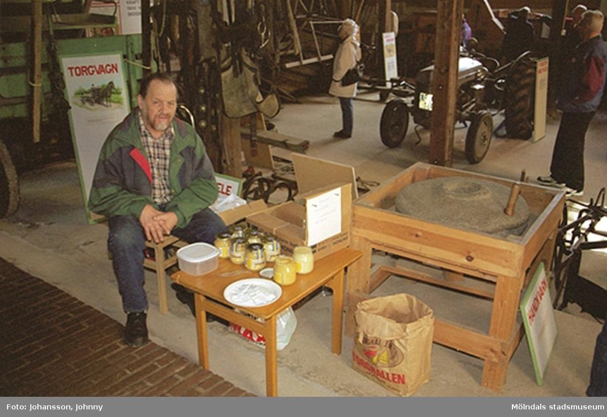 En man säljer honung inne i Lantbruksmuseets lokaler på Götaforsliden 14A.