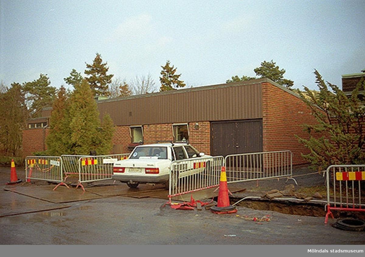 Vy från väster på fastigheterna Ribbstolen och Torpet i Mölndal. Villa med garageinfart och parkerade bilar utanför samt pågående vägrenovering. Oktober 1998 - januari 1999.