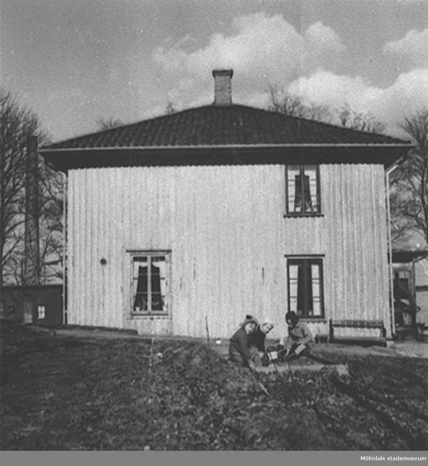 """Huset gjordes om till bostäder åt de estländska arbetarna och där bodde som mest 5-6 familjer samtidigt. Här leker barnen i sandlådan som står utanför villan, slutet av 1950-talet. Hösten 1944 flydde 32.000 estländare från kriget i Estland till Sverige. Ett sextiotal personer tog jobb på August Werners textilfabrik i Lindome. Kvinnorna arbetade i spinneriet och männen i färgeriet.Mer information finns i uppsatsen """"Estländska textilarbetare i Lindome"""" som finns i Mölndals stadsmuseums interna arkiv."""