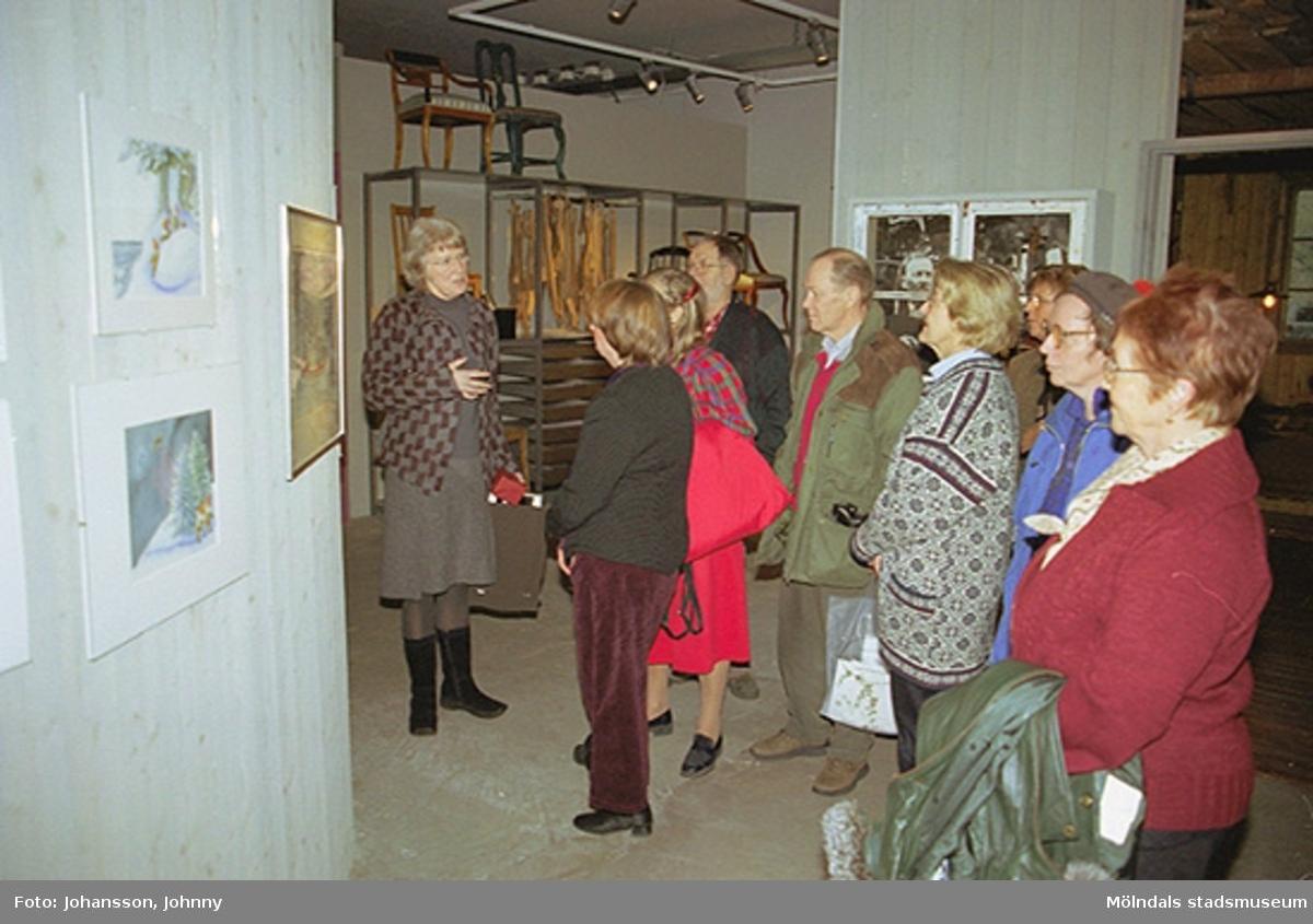 Invigningen på Mölndals museum 2002-11-30.Museichef Mari-Louise Olsson (mörk överdel och vinröda byxor) tittar på målningar tillsammans med besökare.Tomteutställningen: 30/11-02 - 1/1-03.