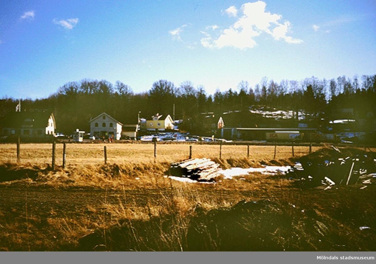 Jordbrukslandskap och ängsmark, mars 1994. I bakgrunden ses villor och en långtradare med släp från ICA.