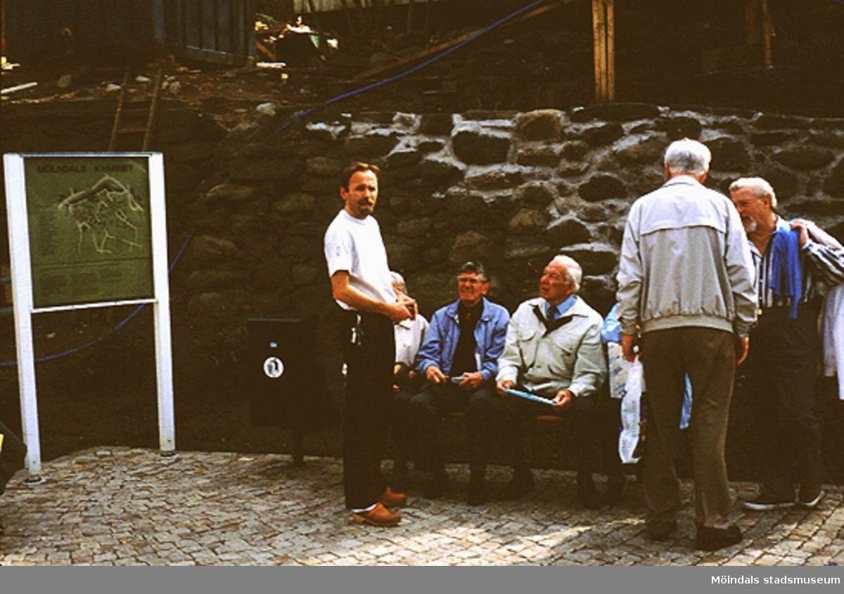 Män och kvinnor vid en bänk på Lyktplatsen i Kvarnbyn. Gatlyktan invigs på Kvarnbydagen 25/4 1993. Sittande, tredje person från vänster är Vigon Olsson. Stående längst till höger är Sven Johnson.