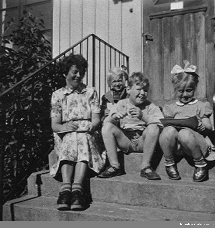 Tre barn och bitr. föreståndaren Margit Emilsson (gift Wannerberg -52) sittande på trappan till Krokslätts daghem, Dalhemsgatan 7 i Krokslätt 1948-1951.