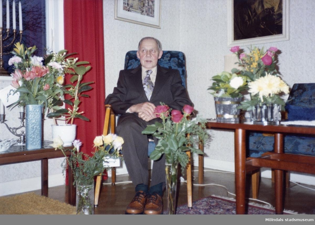 Åke Börjesson firar sin födelsedag, han är fotograferad där han sitter omgiven av blomsterbuketter i vardagsrummet.  1970-tal.