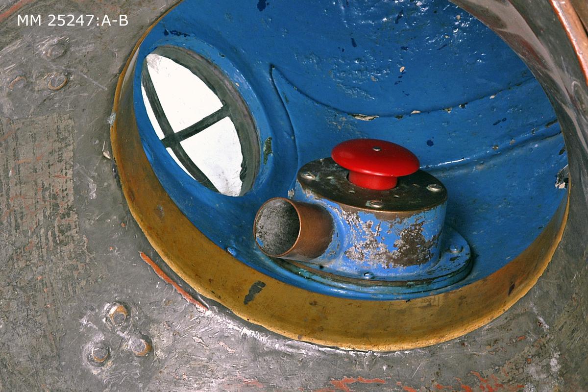 Dykarhjälm i målad metall, sannolikt mässing. Klädd i gummi. Färgen på gummit ursprungligen svart men har blivit grå till största del av slit och tid. Fyra runda fönster placerade i rutmönster. De tre övre fönstren är skyddade av galler iform av ett plus-tecken av rund metall. Det fjärde nedre fönstret öppningsbart och försett med två mässingshandtag med vars hjälp fönstret kan skruvas av från hjälmen. Det öppningsbara fönstret bär spår av grön färg som har skavts av till 80 %. Mot hjälmen på fönstrets infattning sitter en cirka fem millimeter tjock gummipackning. Ovanpå hjälmen sitter en ögla fastsvetsad. Öglan och dess fäste bär spår av grön färg. På sidorna av hjälmen, något nedanför öglan, är två gröna trianglar med spetsen neråt målade i samma gröna färg som på övriga ställen. På sidan sitter en skruv som påminner om ett kugghjul som går att skruva mellan två ytterlägen men inte ta bort. Skruven betydligt nyare än hjälmen i övrigt. Med denna skruv regleras en luftventil som används för att släppa ut koldioxod ur hjälmen. Bakpå hjälmen sitter en anslutning för luftslangen i form av ett L-format rör. På röret sitter ett kopplingsdon som också ser nyare ut än själva hjälmen. På insidan är hjälmen målad i blått. Där sitter bland annat en högtalare och andningsappartur. Inne i hjälmen sitter också en röd knapp. Denna kan tryckas in med hjälp av huvudet och på så vis kan dykaren lufta ut koldioxid ur hjälmen.
