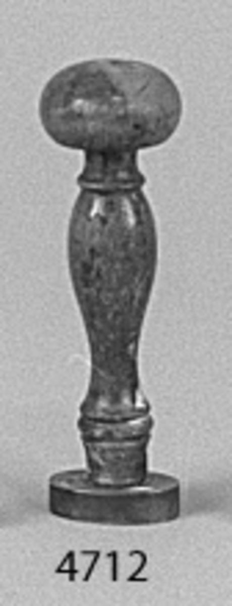 Sigill av mässing. Ovalformat, med svarvat handtag av trä, fernissat. Text: H.M. Najaden.