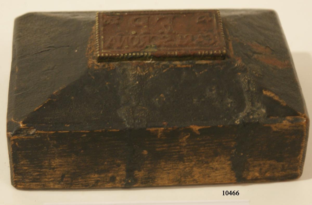 Stämpel av mässing fästad på ovansidan till träblock. Stämpeln rektangulär, 84mm x 50mm. försedd med tandad kant, tryck i upphöjd relief: ?F.P. CARLSCRONA?. Bladrosett i de två övre hörnen. Stämpeln är täckt med röd intorkad färg. Träklossen tillverkad av massivt trä, rektangulärt format. Snedskuren ovansida upp mot stämpeln. Svartmålad.