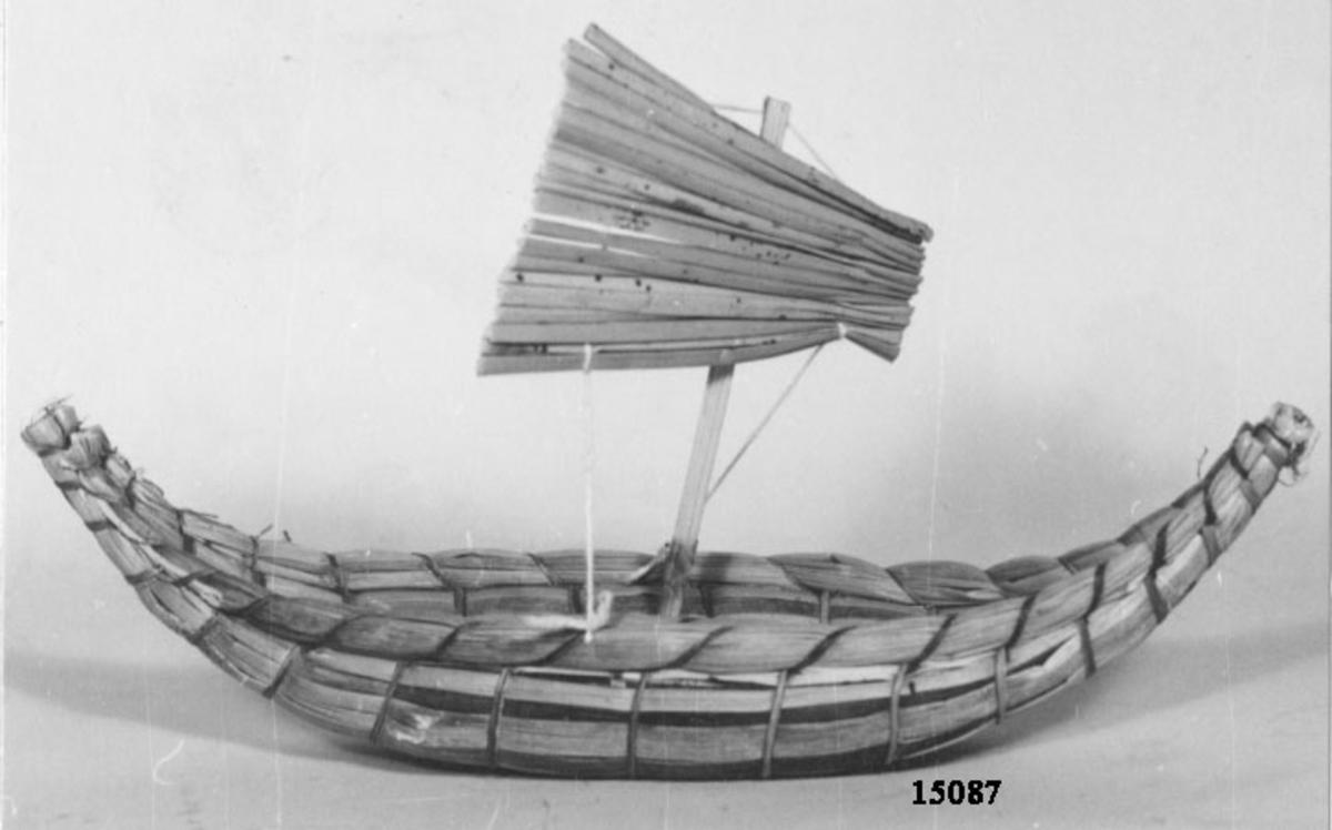 Balsabåt, modell. Består av två hopsurrade flytkroppar av vass, som vardera relingen har en míndre vasskropp. Båten har uppsvängd för- och akterstäv samt har mast med segel av vass.