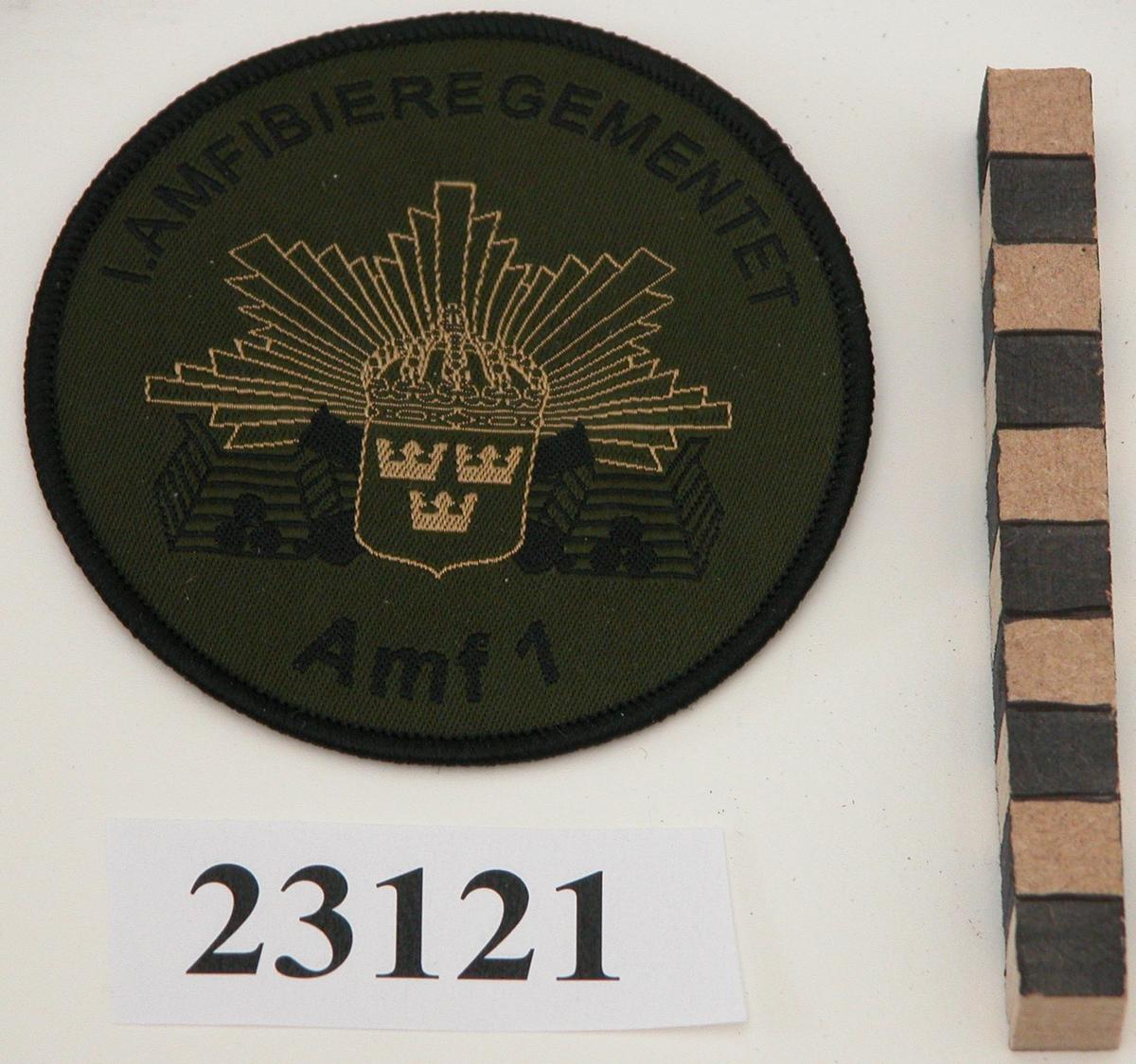 """Ett cirkelrunt märke av mörkgrönt tyg försett med broderad text i svart """"1.AMFIBIEREGEMENTET"""" OCH """"Amf 1"""" övererst resp nederst. I mitten en med guldtråd broderad vapensköld med tre kronor, krönt av kunglig krona lagd över två korslagda kanoner i svart brodyr. Bakom skölden kantiga guldstrålar samt stiliserad befästningsmur i svart brodyr. Framför muren på vardera sidan av skölden tre runda, svarta kanonkulor. Märket kantat med svart tråd. På baksidan påstruket vitt flisselin och ett fastlimmat märke med guldbotten på vilket det med svart tryckfärg står """"for best quality and design BACKHAUSEN AB Box 4105 30004 Halmstad Sweden Telefon 035-213700 Telefax 035 214440 E-post: info@backhausen.se www.backhausen.se"""" Till vänster om texten en tryckt pegas i svart."""