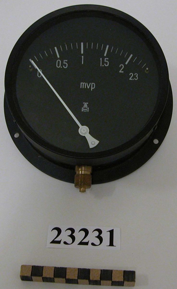 Nivåmätare, cirkelrund form, hölje av svartlackad plåt. Tavlan svart med en vit visare samt gradering och siffror i vitt. Graderad 0 - 2.3. Under gradering, mvp i vitt ( meter vatten pelare ) samt NAF. Mätarens bakkant är platt och försedd med hål för uppmontering. Gängad ventil i mässing.