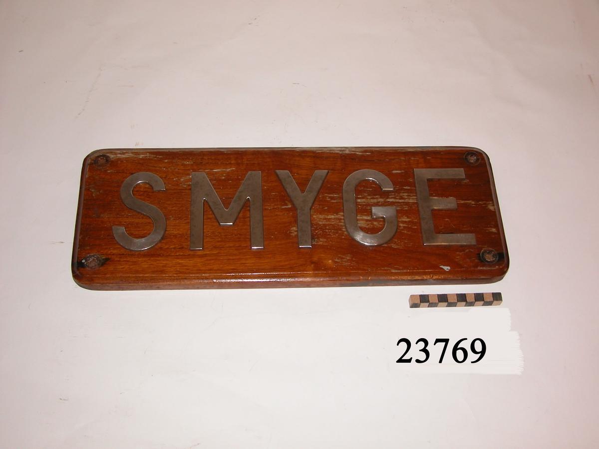 """Rektangulär, lackad träplatta med rundade hörn och falsad kant. På framsidan versala bokstäver av rostfritt stål """" SMYGE """" som är fastskruvade från brädans baksida. Bokstävernas höjd: 100 mm. Hål i plattans vardera hörn för uppmontering."""
