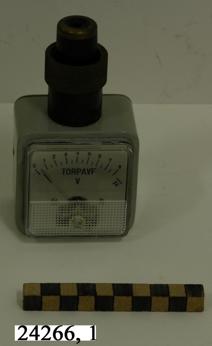 """Rektangulär, gråmålad nederdel med mätare märkt """"TORPAVF"""", """"V"""" graderad 0-8. På ovansidan sitter delen som sätts på torpedtuben och låses med en gängad hylsa. Apparaten märkt med tre kronor och typ 13600. På undersidan sitter en etikett märkt """"Provad: 27/9 74, Sign. CH-m, Senaste utlämn. datum   19""""."""