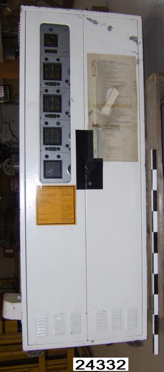 """Apparat lackerad med grå """"krympfärg"""", framsidan delvis vitmålad. Framsida med två dörrar. På vänster dörr sitter ett klistermärke med larmsignaler vid stridsberedskaper. På höger dörr sitter två maskinskrivna papper fasttejpade innehållande PM för uppstartning för maskin HMS Hasslö. Avklippta kablar på ovansidan av apparaten. Apparaten har nio konsoller. På den övre sitter ett papperskort visande strömstyrkor för magnetskydd. De övriga konsollerna har bland annat manövervred och visare för kalibrering och strömreglering."""