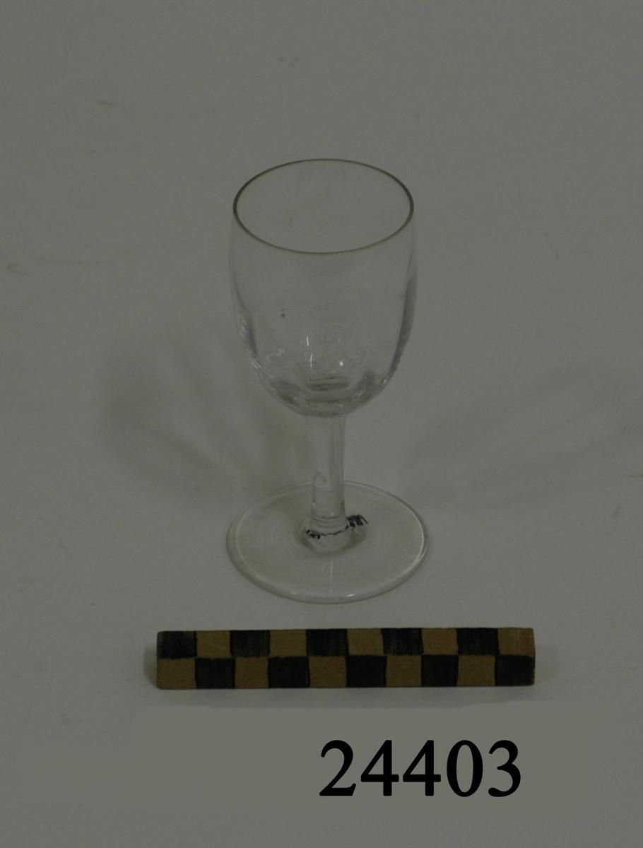 Likör eller sherryglas bestående av välvd smal cylindrisk kupa med lodräta vågmönster. Smalt runt ben och rund plan fot. På kupan graverad dekor: ett krönt stockankare med monogram R M ( Reale Marina = Kungliga Flottan ). Diameter: 47 mm, glaset   D = 55 mm fot