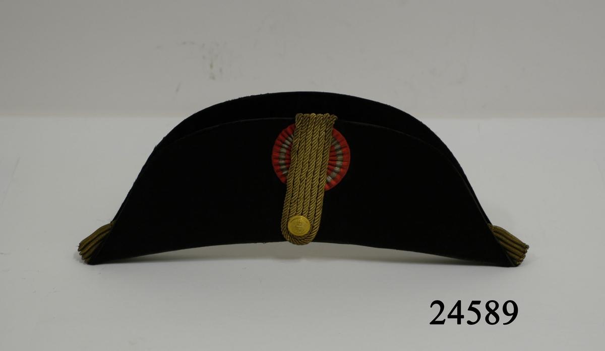 Svart paradhatt, halvmånformad med två stora uppvikta brätten. Hatten är tilllvekad av styv kartong, överklädd med svart silkfälb. Kullen är ihopvikbar. Det ena brättet försett med sidenkokad i rött och silver. Över denna tre stycken vikta guldsnoddar fästa med förgylld knapp med stockankare och kunglig krona. I hattens hörn, ändar, guldbuljoner. På insidan klädd med vitt sidentyg. Svettrem av ljust läder. Stämel: Kunglig Hov Guldtrekker, Kunglig Svensk Hovleverantör C.L Seifert Köpenhamn.