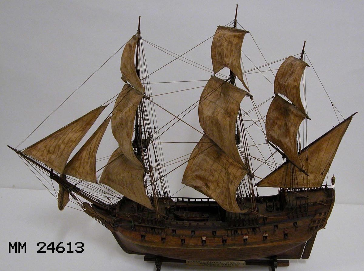 """Modell och stativ. På stativet finns texten """"FARTYG AF SWENSKA OST.INDISKA COMPAGNIETS FLOTTA. ÅR 1767 BYGD AV VICTOR CARLSON""""."""
