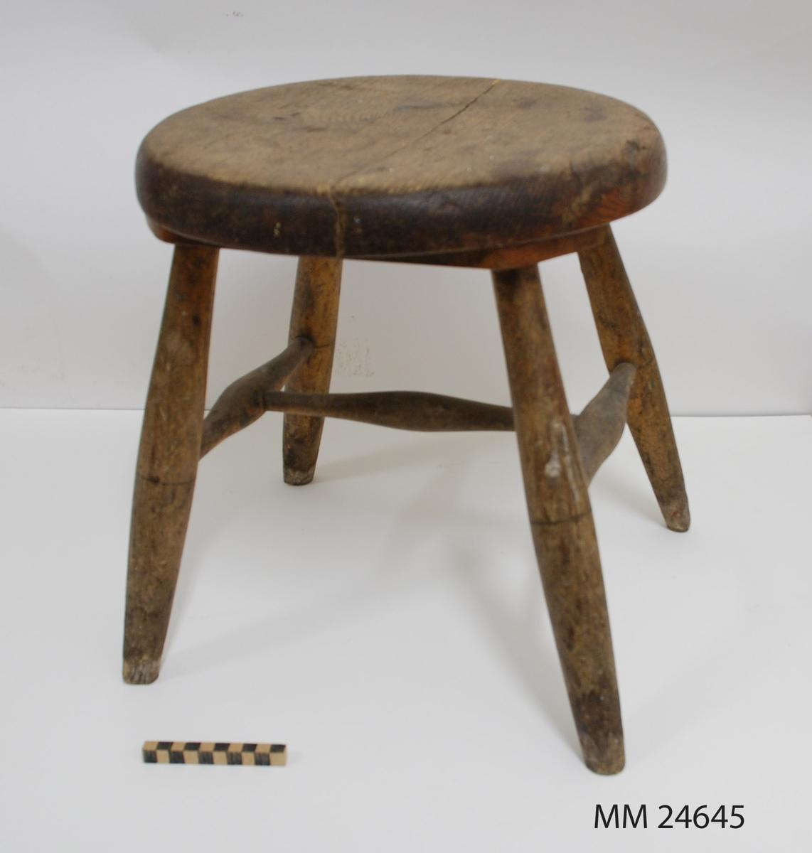 """Pall av trä med fyra ben. Runda ben med svarvade träslåar, sk. H-kryss. Benen tappade i två reglar under sitsen. Reglarna skruvade i sitsen. Rund sits, spricka genom hela sitsen. Märkning i blyerts under sitsen: """"1868-11-4""""."""
