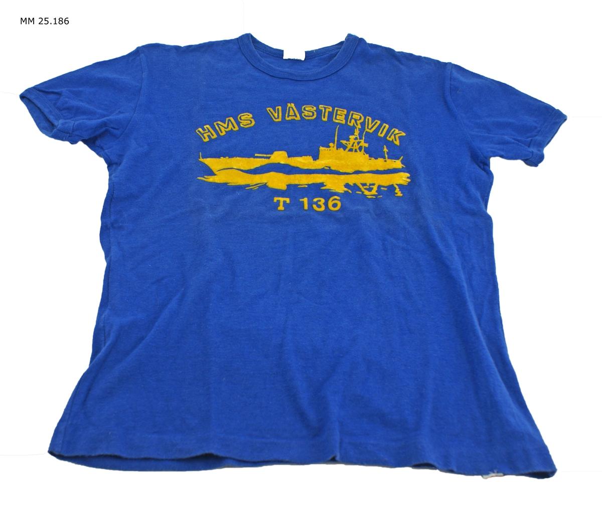 """Marinblå kortärmad t-shirt med gult tryck i plyschaktigt material. Text: """"HMS Västervik T 136"""" och en torpedbåt till sjöss."""