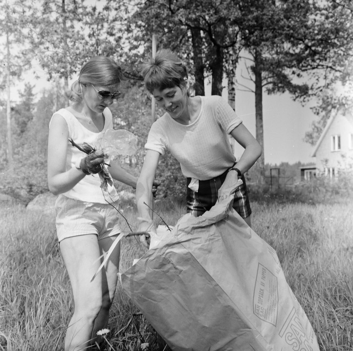 Margareta Martinsson och okänd kvinna i Söderfors husmodersförening plockar skräp