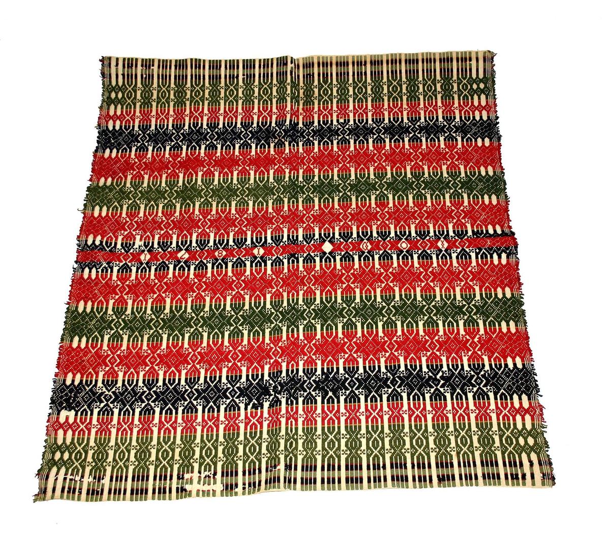 Form: Vove i mønster med grøne, blå og (23) 15: raude striper. På midten vove I.O.D. 1871 (Ingeborg Olsdatter Haukaas). Vart brukt som sengeteppe og til å ha rundt barn når dei skulle døypast.