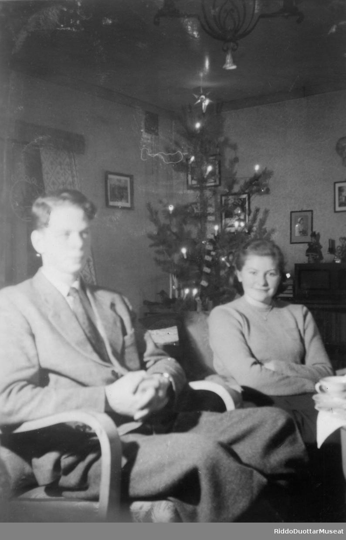 Dievdoolmmoš ja nissonolmmoš cohkkaba beavdde- guoras. En mann og en kvinne sitter ved stuebordet.