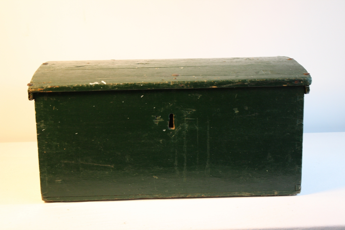 Kiste med svakt bua lok. Handtak i metall på begge sider. Metallnagler i lok.  Den er målt grøn. Sett saman med sinking. raudmålt inni. Spor etter at det har vore ein leddik.