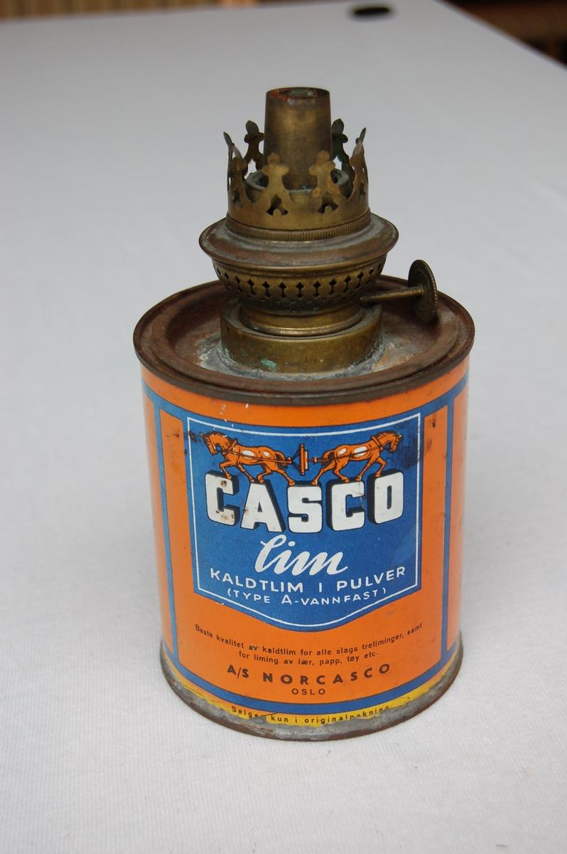 Parafin- oljelampe som er samansatt av ein parfinbrennar og ein casco limboks. Brennaren er lodda fast i lokket på limboksen. Over brennaren har det vore eit lampeglas som gav stabil og jevn brenning. Limboksen er oransje med detaljer.