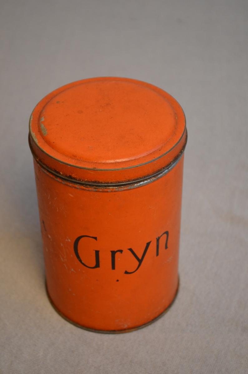 Rund boks for oppbevaring av matvarer. Oransje farge. Det står Gryn på boksen. Målinga er skrapt av enkelte plassar. Det er framleis risengryn i boksen.