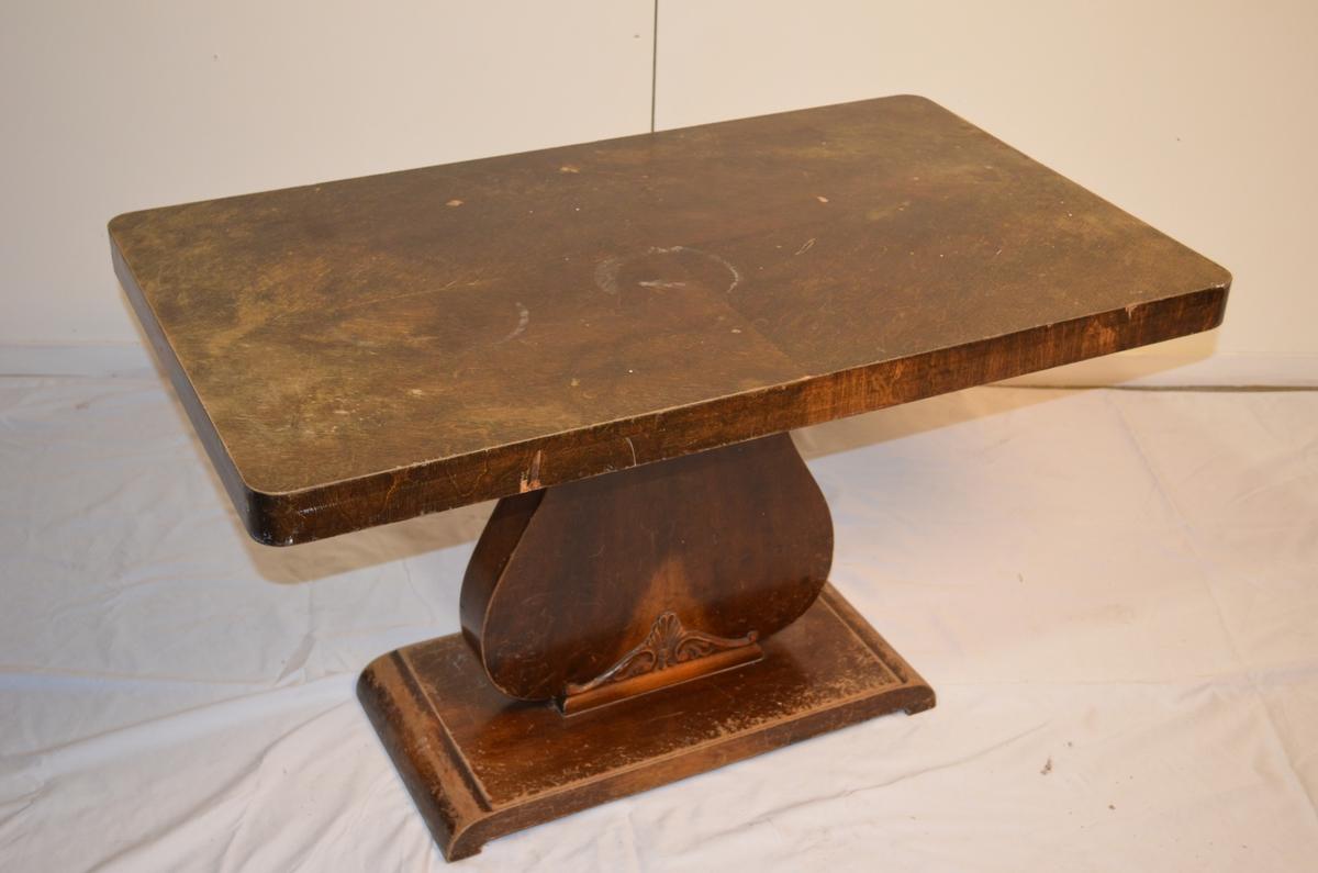 Rektangulert stuebord med ein fot. Nederst på foten er det limt fast utskjæring av tre. Flekkar og misfarging på bordplata.