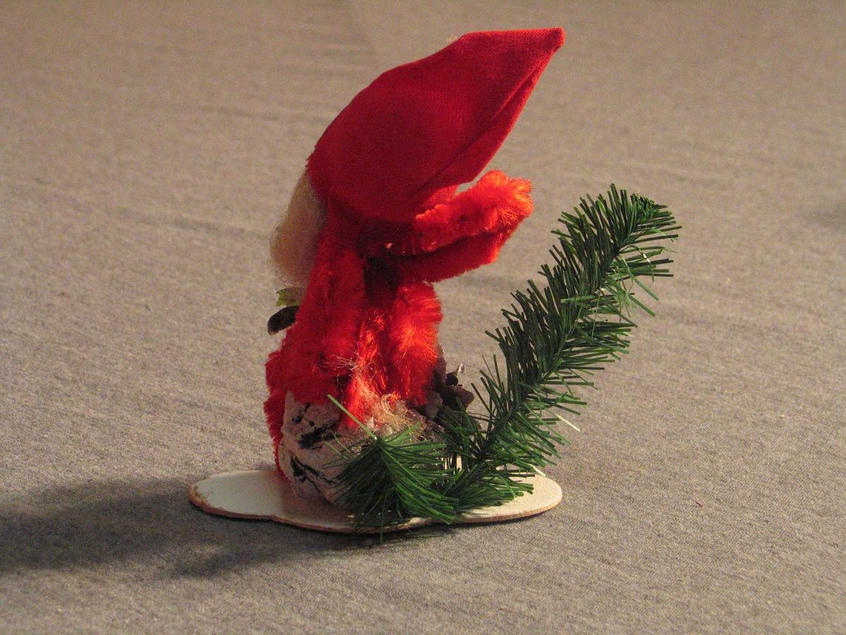 Julenisse av piperensar, sit på ei furukongle med snøglitter. Nissehovudet er av pappmache, måla ansikt, langt skjegg. Nissehue av stoff. Plastimitasjonar av granbar og tytebærlyng.  Figuren er limt på ei papplate.