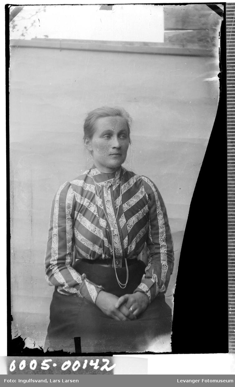 Portrett av kvinne i iført bluse og med klokkekjede.