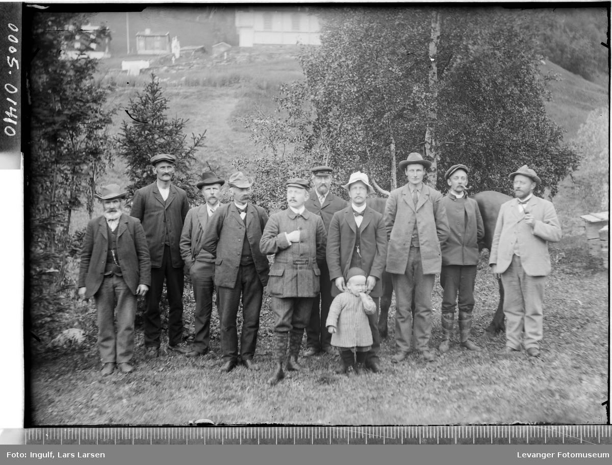 Gruppebilde av ti menn og et barn.