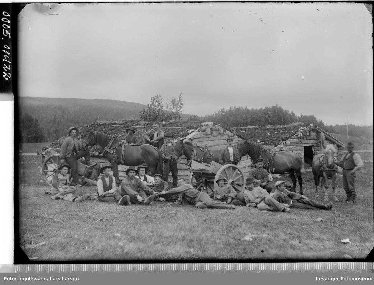 Gruppebilde av menn, hester og bikkkjærrer foran løer med torvtak.