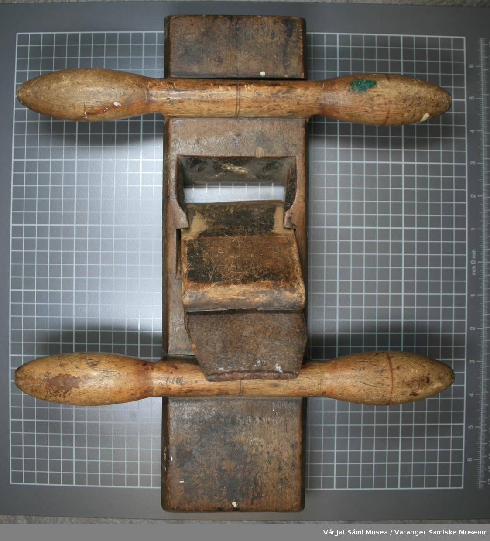 Tomanns høvel, kalt oksehøvel. Kilen er festet i bladet med skrue. Fargen på høvelen er mørkebrun. Begge håndtakene er løse.