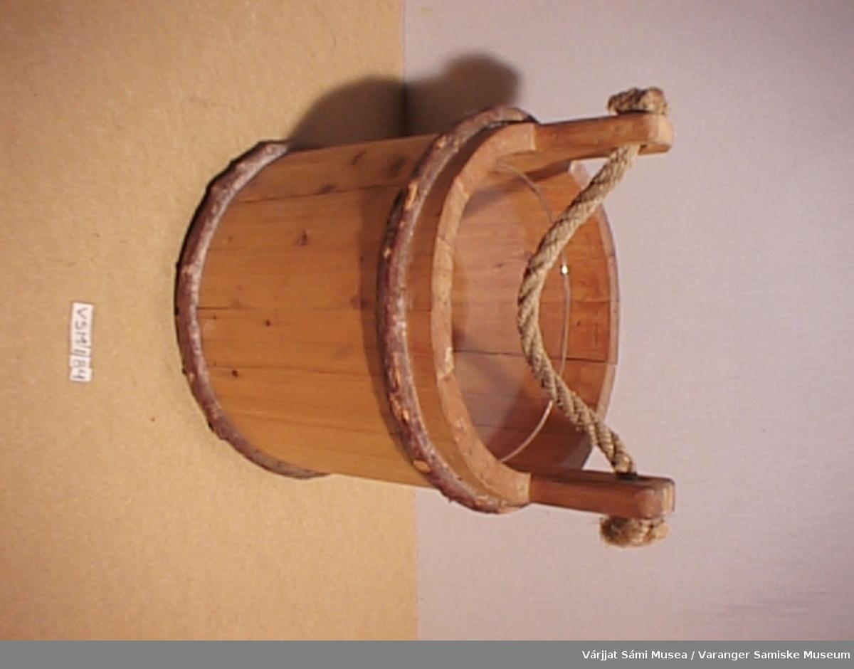 Moderne reproduksjon av trebøtte av gammel type. Satt sammen av staver som er festet sammen med bånd. To gjennomhullete håndtak på hver side med et tau mellom.
