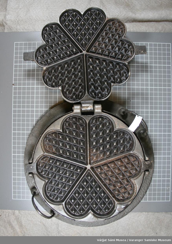 Vaffeljern av metall, steker fem hjerters vaffelplater. To håndtak på siden og et på toppen.