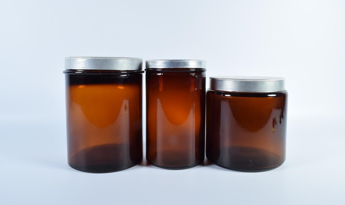 Tre brune sylindriske glass med skrulokk i metallokk i forskjellig størrelse.