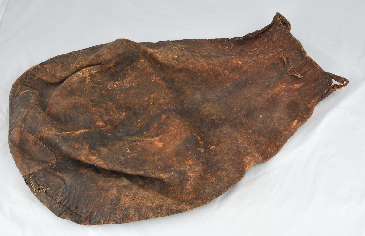 Sekk sydd av to pæreforma skinnstykke. 4 innfelte kilar i opninga. Forsterking i botn og andre reparasjonar. Opninga er smal, 30 cm i tverrmål. Sekken utvidar seg til ei breidde på 63 cm. Avrunding ned mot botn. Restar etter lita skinnhempe i øvre kant.