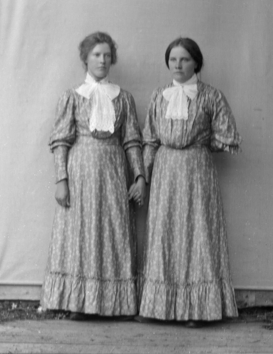 To kvinner i helfigur kledd i mønstrete kjoler, stående foran hvitt lerret på husvegg