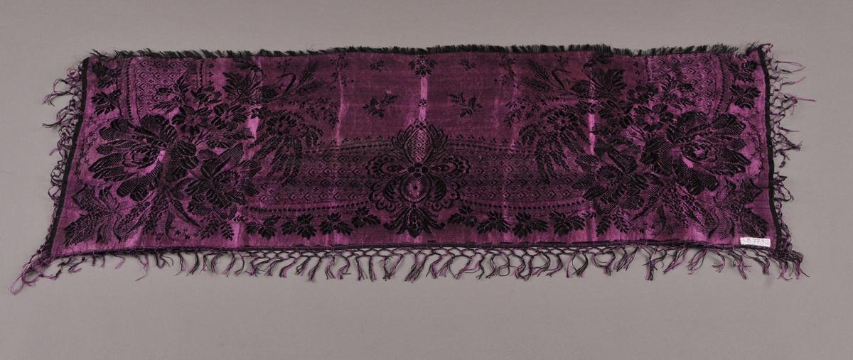 Damaskvove silketørkle i svart og fiolett med rosemønster. Knytte frynser langs tre sider. Rett avklipt og med to cm lange frynser langs fjerde sida. Rektangulært.