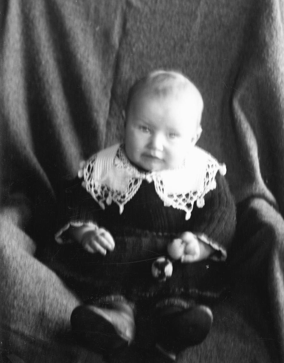 Spedbarn i stol, fotografert innendørs