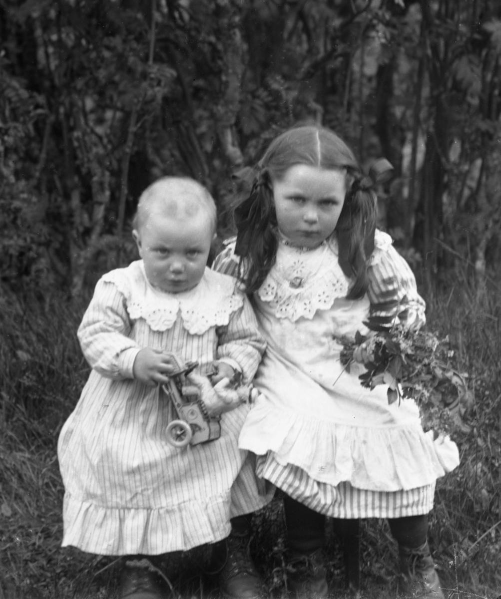 Liten jente med musefletter, holder blomsterbukett, samt mindre barn med lekebil, begge kledd i hvite kjoler. Gress og busker i bakgrunnen